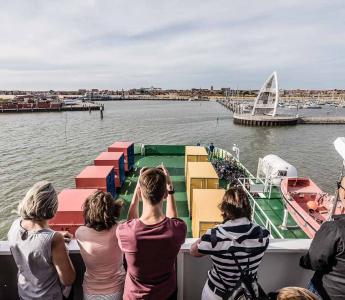 Touristen auf dem Deck der Fähre von der Reederei Frisia bei der Ankunft auf der Insel Juist